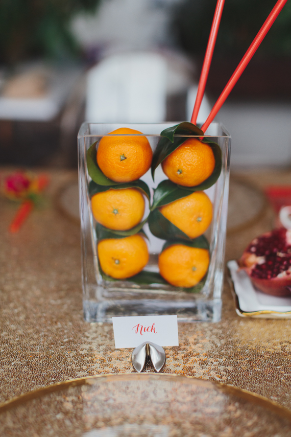 Decorating with tangerines at a Chic Gold and Red Chinese New Year Dinner Party. See more at Rebecca Chan Weddings and Events http://www.rebeccachan.ca