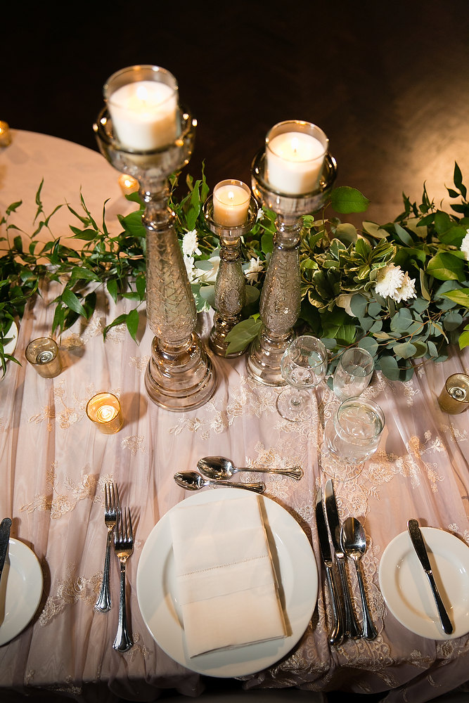 Classic ivory and champagne wedding head table decor of tall candle sticks and delicate lace linen at Liberty Grand. See more at Rebecca Chan Weddings and Events http://www.rebeccachan.ca