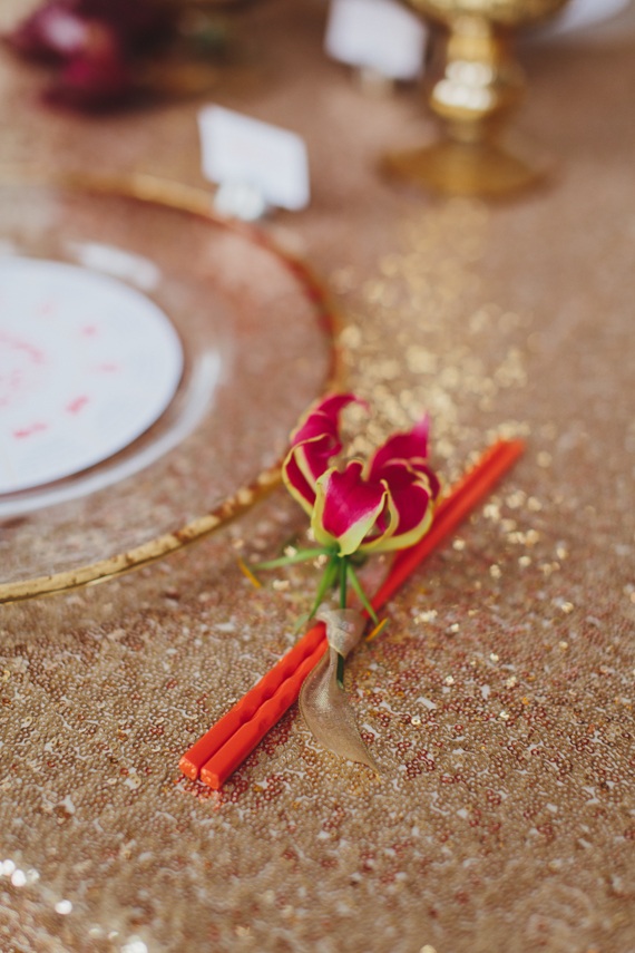 Gloriosa lily accent on red chopsticks on gold sequin linen. Red and gold dinner party inspiration. See more at Rebecca Chan Weddings and Events http://www.rebeccachan.ca