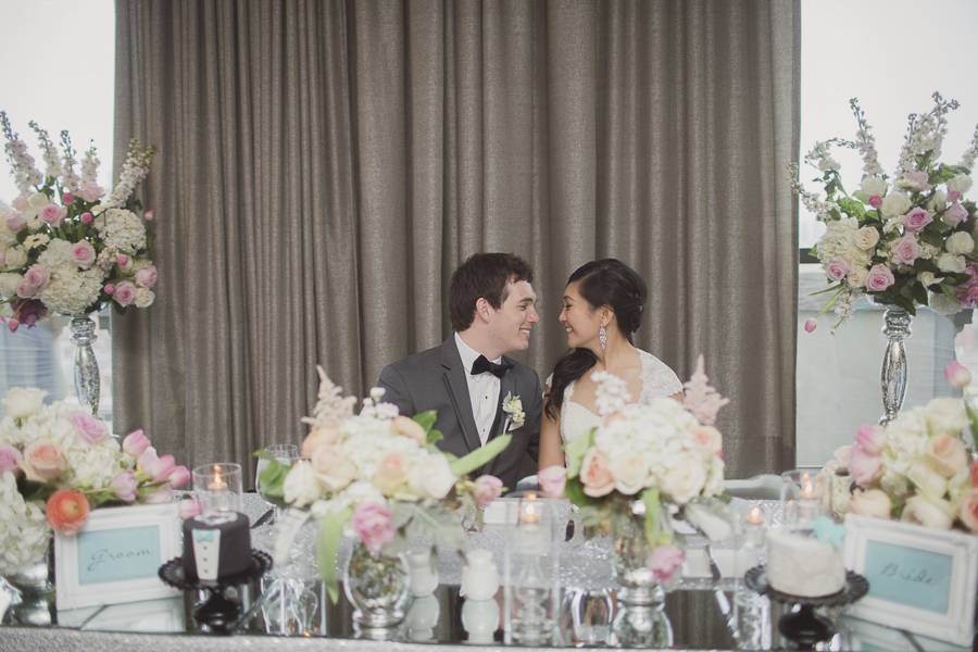 Bride and groom share a moment at their floral-filled sweet heart table. See more at Rebecca Chan Weddings and Events http://www.rebeccachan.ca