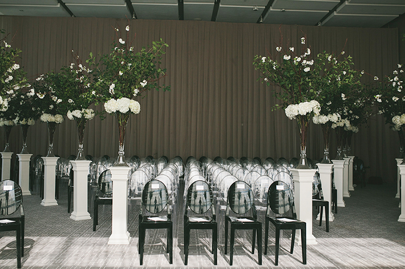Black ghost chairs line the aisle at this modern black-tie wedding ceremony, as seen in Wedluxe. Planner: Rebecca Chan Weddings and Events www.rebeccachan.ca To see more, visit www.rebeccachan.ca