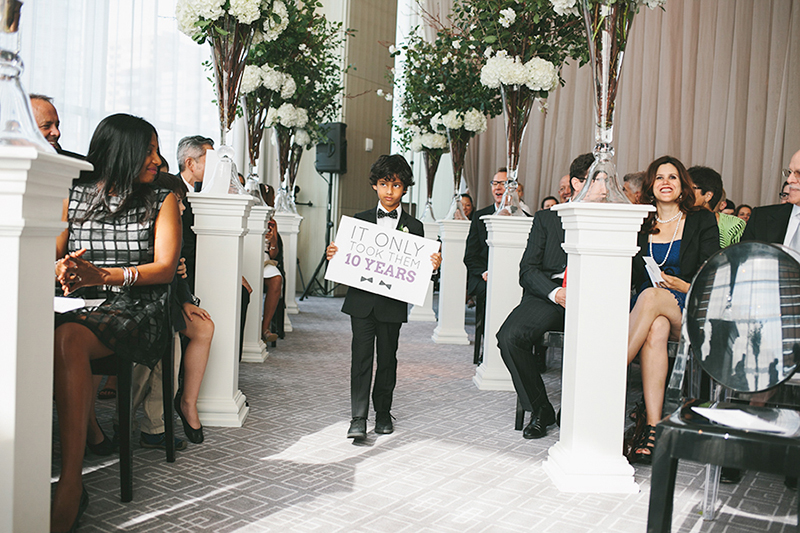 Ring boy with sign at a modern black-tie affair, as seen in Wedluxe. Planner: Rebecca Chan Weddings and Events www.rebeccachan.ca To see more, visit www.rebeccachan.ca