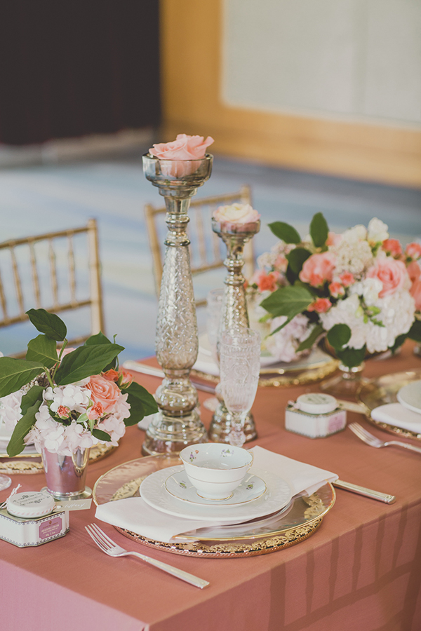 Loving this tablescape of flowers in candlesticks, vintage teacups and gold chargers. Coral and Gold Wedding Inspiration - See more at Rebecca Chan Weddings and Events www.rebeccachan.ca