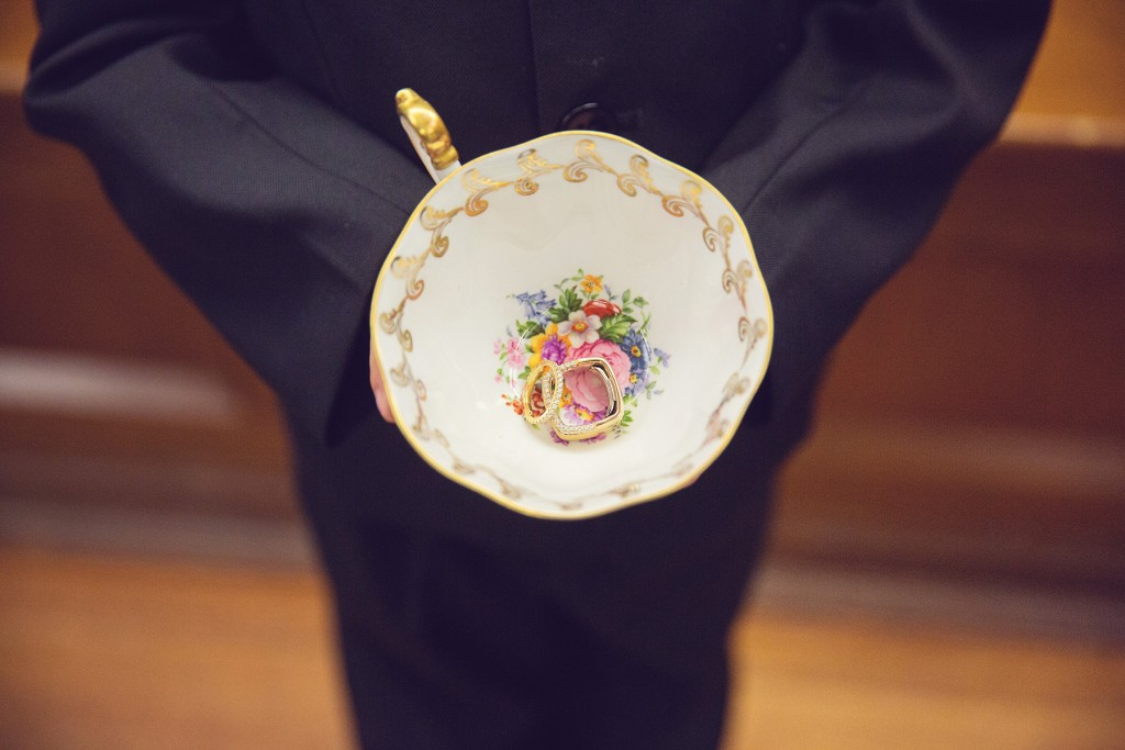 Elegant vintage-inspired purple and gold wedding - Ring boy holding rings in a tea cup