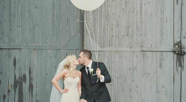 The bride and groom take fun photos with giant balloons. www.rebeccachan.ca