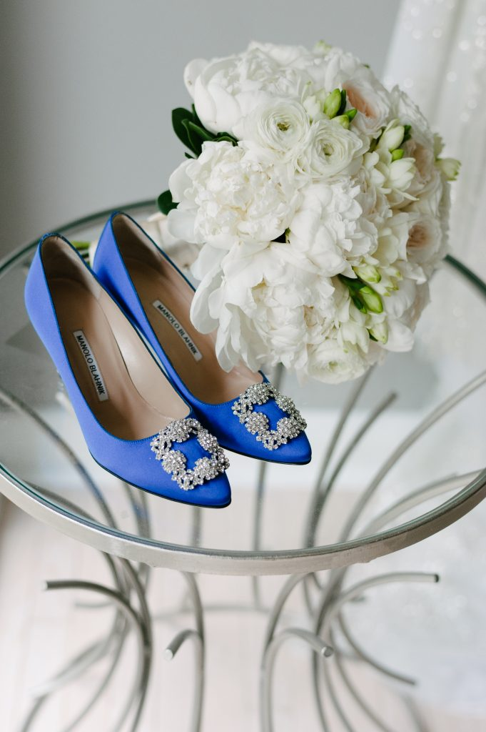 White bridal bouquet and blue Manolo Blahnik shoes.