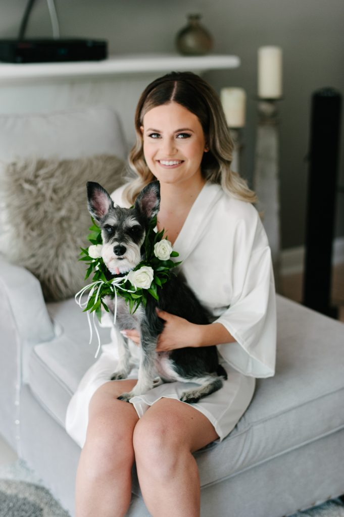 Bride with her dog, wearing a floral garland.