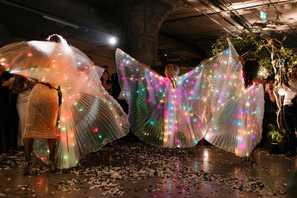 Cabaret dancers with LED Wings at an urban wedding.